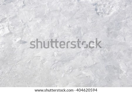 Closeup view on beautiful textured winter seaon background of cold frozen water in shiny white ice with snow and no people - stock photo