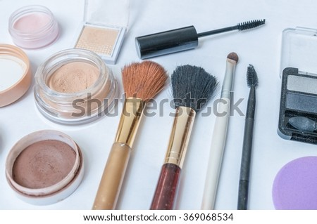 Closeup view on cosmetics, makeup and brushes on white background.
