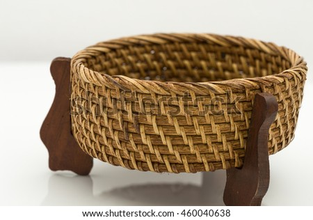 Closeup view on rattan basket with three wooden legs and plywood base. Isolated on white background.