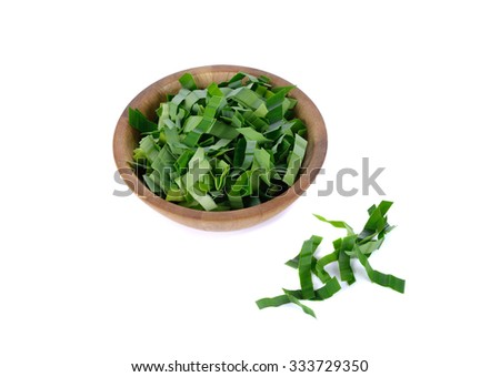 Closeup view on shredded pandan leaf in a wooden bowl at left side with some outside the bowl. The leaf is use as herbal tea for its strong sweet fragrance and medicinal benefits. White background. - stock photo