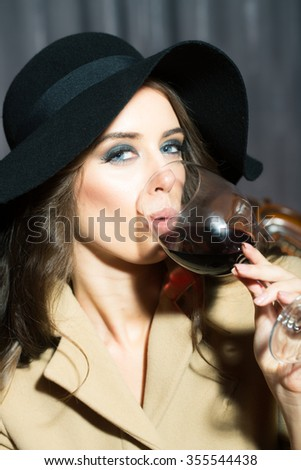 Closeup view portrait of one attractive sensual sexy woman with curly hair and bright makeup in round black tweed hat drinking red wine from glass indoor on blurred backdrop, vertical picture - stock photo