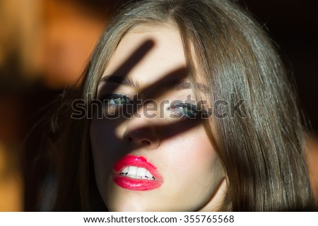 Closeup view portrait of one attractive sensual strange pensive young stylish woman with bright red lip gloss in black and white blouse with hand shade on face looking forward, horizontal picture - stock photo