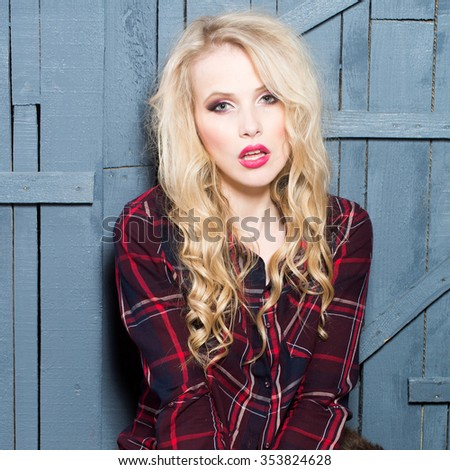 Closeup view portrait of one attractive sexual passionate blonde woman with long curly hair sitting in studio in checkered shirt looking forward on wooden background, horizontal picture - stock photo