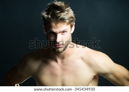 Closeup view portrait of one handsome young muscular naked sexy macho man with short hair bare chest and beautiful body standing in studio on black backdrop, horizontal picture - stock photo