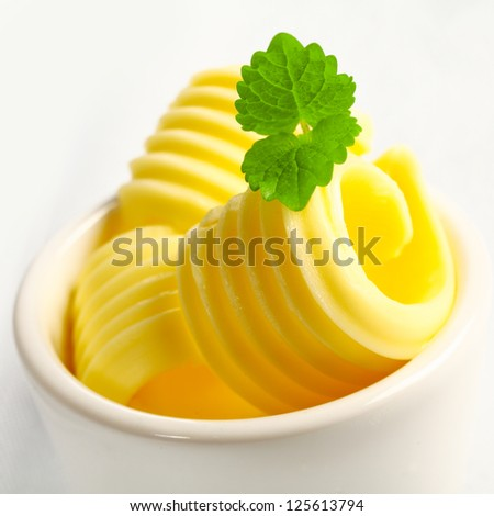 Closeup view with shallow dof of slices of rolled golden butter for a catered event or restaurant in a small ceramic dish garnished with mint - stock photo