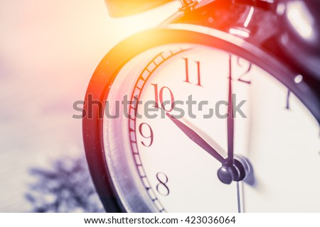 closeup vintage clock selective focus at number 10 o'clock with sun light vintage color tone for postcard. - stock photo