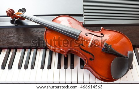 Closeup violin on piano. Concept of music background. Top view.