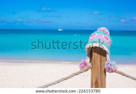 Closeup warm knitted cap on fence at tropical beach