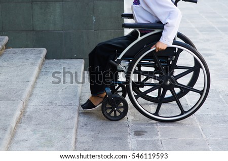 Closeup wheels of wheelchair with woman sitting in it, physical handicapped concept