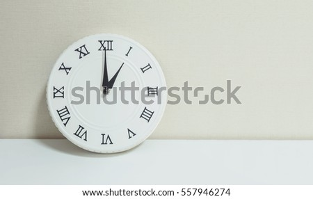 Closeup white clock for decorate show 1 o'clock on white wood desk and cream wallpaper textured background with copy space