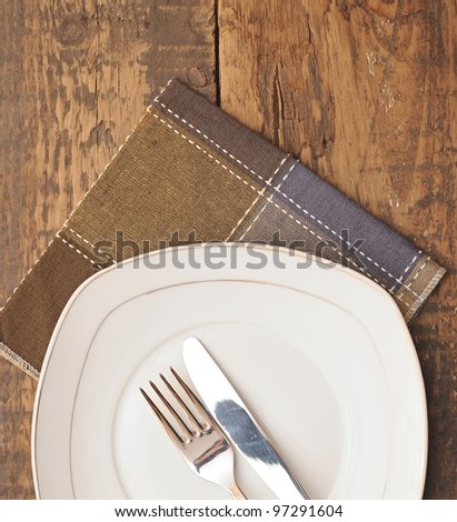 closeup white empty plate with brown napkin, knife and fork on wood table - stock photo