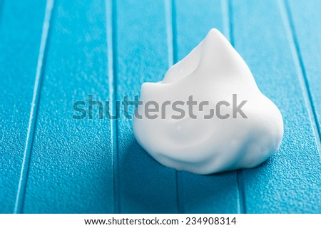 closeup white hair mousse on blue background - stock photo