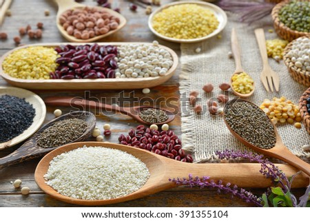 Closeup white sesame with various lagumes on the table - stock photo