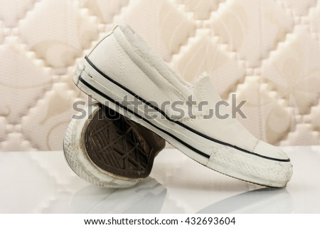 closeup white women canvas sneakers without laces - stock photo