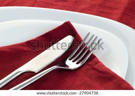closeup with knife and fork on dark red napkin