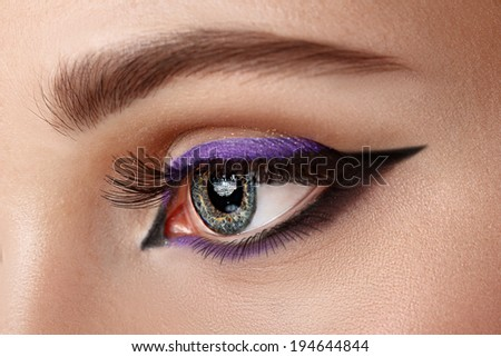 closeup woman eye with makeup - arrow black and lilac - stock photo