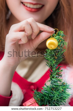 Closeup woman hand decorating Christmas tree with yellow ball