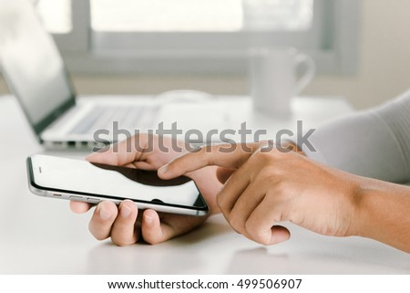 closeup woman hand using phone on workspace in office
