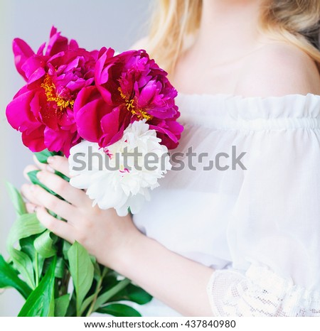 Closeup woman hands holding pink and white peonies
