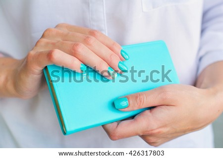 Closeup woman hands with elegant turquoise manicure holding blue diary
