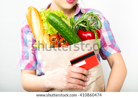 Closeup woman holding paper bag with fresh food and credit card, detail - stock photo