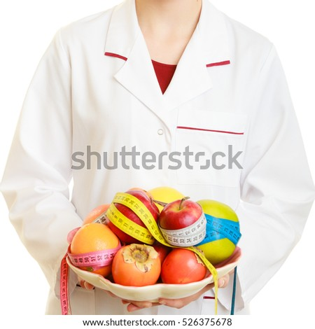 Closeup woman in white lab coat holding fruits and colorful measure tapes isolated. Doctor dietitian recommending healthy food. Dieting
