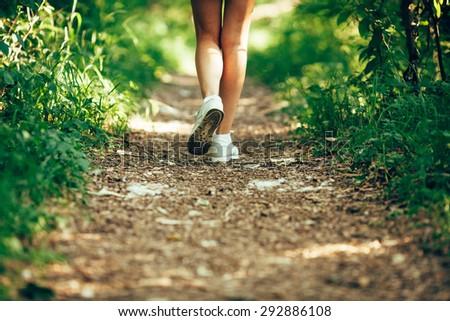 closeup woman runner shoe on park trail - stock photo