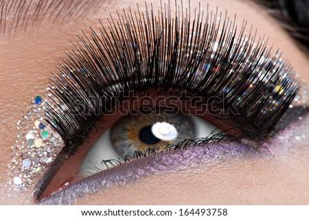 Closeup woman's eye with long black false eyelashes and  creative fashion bright makeup - stock photo