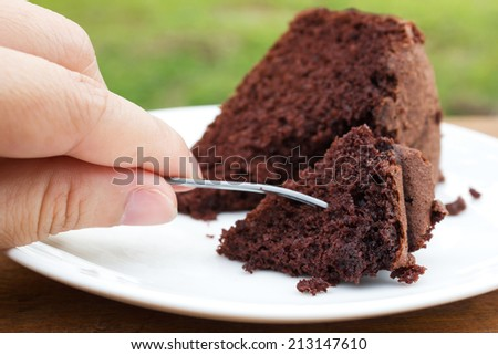 Closeup Woman's hand hold a fork to slice of chocolate cake. - stock photo