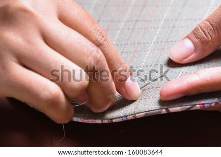 Closeup woman's hand sewing quilt - stock photo