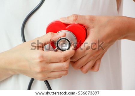 Closeup Women with stethoscope examining red heart  on white background,diagnostic exam for heart