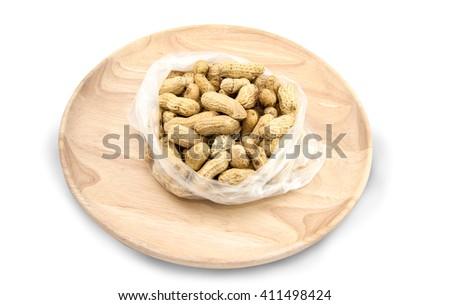 Closeup wooden dish of Peanut, Ground nut, Earth nut, Goober nut, Pindar nut, Monkey nut on white background; Top view of Peanut, Ground nut, Earth nut, Goober nut, Pindar nut, Monkey nut. - stock photo