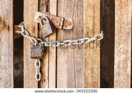 closeup wooden door lock with padlock and chain - stock photo