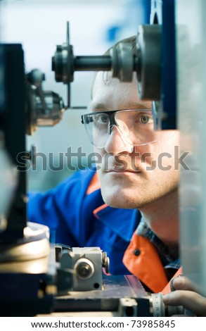 Closeup worker in uniform and protective glasses working on sharpening machine tool - stock photo
