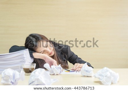 Closeup working woman sleeping after she tired from her work with work paper and document file on blurred wooden desk and wall textured background in the meeting room , tired working woman concept