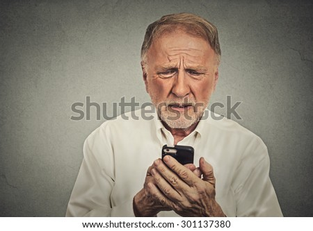 Closeup worried elderly man looking at his smart phone isolated on gray wall background  - stock photo