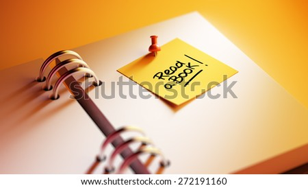 Closeup Yellow Sticky Note paste it in a notebook setting an appointment. The words Read a book written on a white notebook to remind you an important appointment. - stock photo