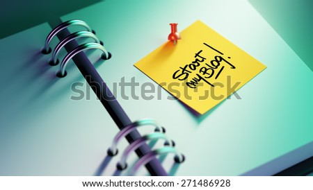 Closeup Yellow Sticky Note paste it in a notebook setting an appointment. The words Start my Blog written on a white notebook to remind you an important appointment. - stock photo