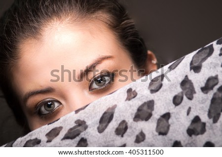 Closeup young brunette model posing with grey brown scarf covering half her face revealing beautiful eyes only, dark background - stock photo