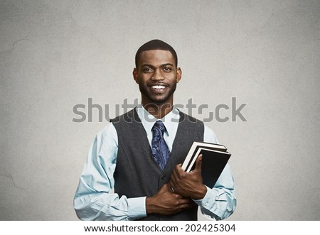 Closeup young smart, happy, smiling handsome man holding books, prepared, ready to ace his exam test finals, isolated black, grey background. Positive human facial expression feeling, emotion attitude - stock photo