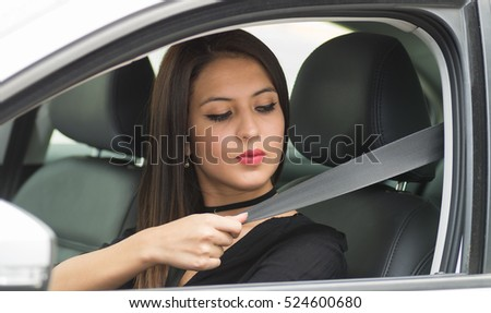 Closeup young woman sitting in car putting on seatbelt, as seen from outside drivers window, female driver concept