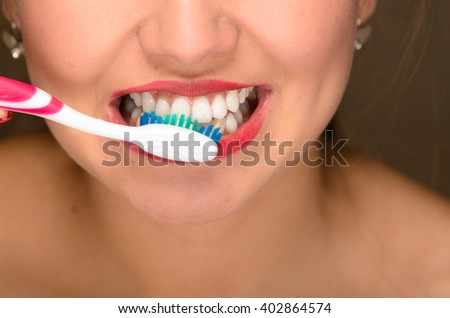 Closeup young womans mouth and white teeth, using toothbrush.