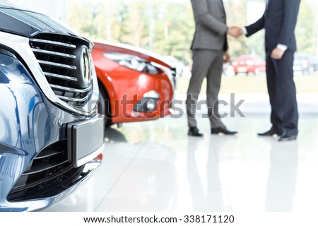 Closing the deal. Selective focus on the car customer shaking hands with dealer on the background - stock photo