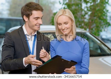 Closing the deal. Young handsome sales representative is helping his client to fill in important purchasing forms.  - stock photo