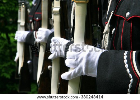 Closup detailed photoof the soldiers hands in gloves on a bayonet rifle in rest position during a military parade. Selective focus - stock photo