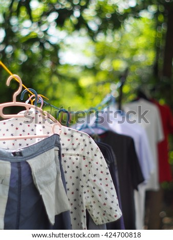 cloth clothing hanger row with colorful plastic hanging close-up with variety colour t-shirts hanging outdoor with dark green bokeh background