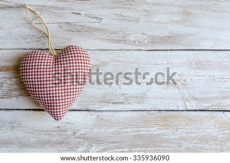 Cloth heart on wooden board - stock photo