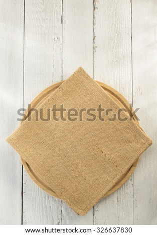 cloth napkin and cutting board on wooden background - stock photo