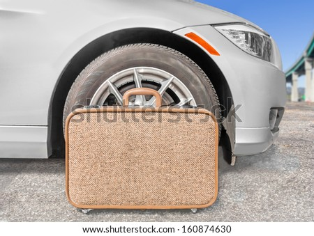 Cloth suitcase and car tire wheel. Brown carry on size roller bag in front of sedan parked on asphalt surface. Elevated freeway overpass in blurred background. Blue sky. Traveling concept. Horizontal. - stock photo