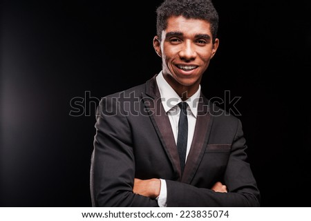 Clothed in confidence. Smiling young Afro-American man keeping arms crossed while standing against black background - stock photo